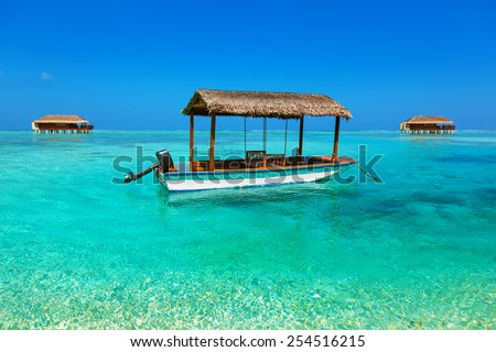 Boat and bungalow on Maldives island - nature travel background