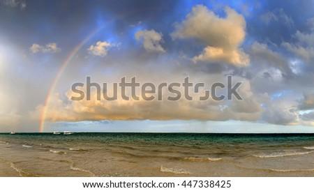 Boat and rainbow in ocean, Indian ocean - stock photo