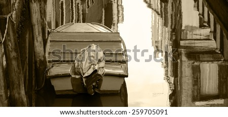 Boat and reflection of houses in the water. Narrow canal in Venice.  Aged photo. Sepia. - stock photo