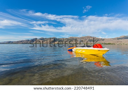 Boat and water tube on the Osoyoos lake in Canada with mountains and blue sky - stock photo