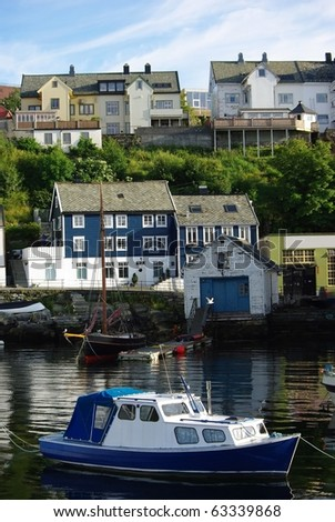 Boat and yacht berthed in front of the house by the sea in Alesund, Norway - stock photo