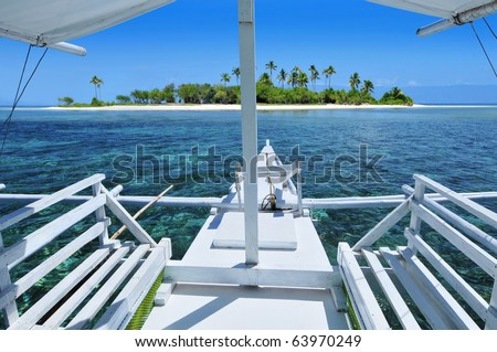 Boat approaching a beautiful pristine tropical island beach. - stock photo