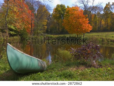 boat ashore a pond in upstate New York, with fall foliage - stock photo
