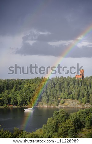 Boat at the end of the rainbow - stock photo