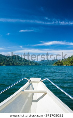 boat bow cruising on calm water, islands ahead. Belum resort, Banding, Temenggor Lake.