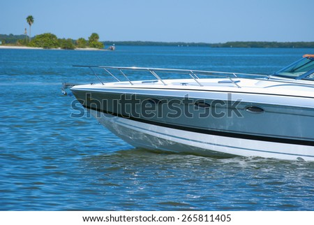 Boat bow of new boat idling through beautiful blue water - stock photo
