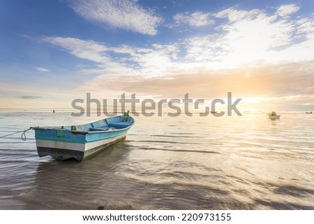 boat by the huahin beachside during beautiful sunrise wih flare effect
