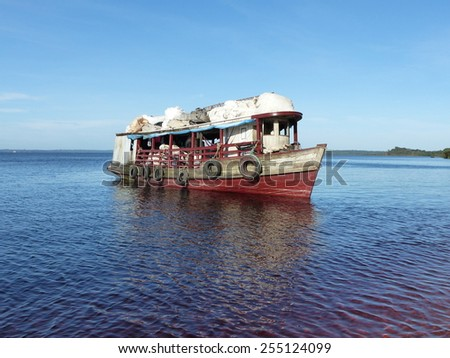 Boat collects empty cans on the beach of Praia da Lua near Manaus. Amazona, Brazil - stock photo