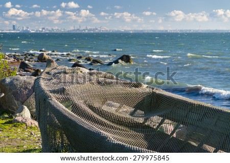 Boat covered by fisherman net at seashore and modern cityscape on background - stock photo