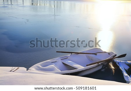 Boat covered with snow near the shore covered with a layer of untouched snow.  in the background begins to freeze, covered with thin ice river.Beautiful frosty winter morning, mist, soft pink light.