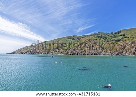 Boat crossing San Luis Obispo Bay with aquamarine waters, gentle seas, & light breeze. In the background is coastal hills and steep cliffs. An Idyllic daydream. Photographed near Avila Beach, CA.