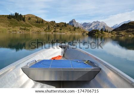 Boat cruising a mountain lake. Switzerland  - stock photo