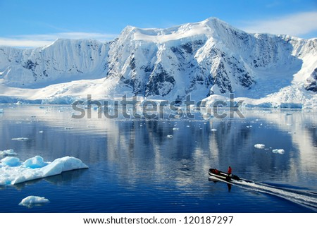 boat dwarfed by antarctic mountains