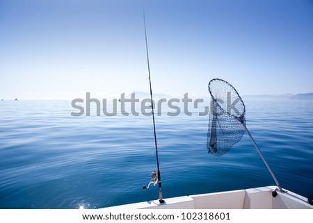 boat fishing rod and landing net in mediterranean blue sea - stock photo