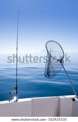 boat fishing rod and landing net in mediterranean blue sea - stock photo