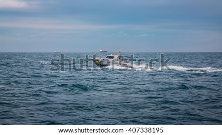 boat floating on the waves of the sea against the backdrop of merchant ships