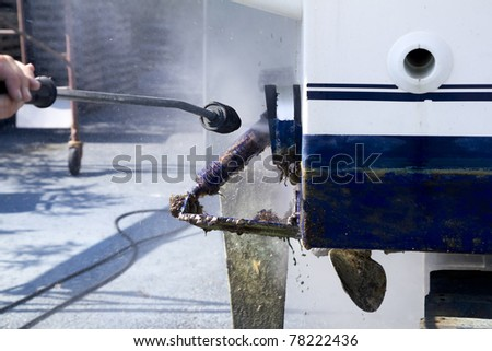 Boat hull cleaning water pressure washer barnacles antifouling and seaweed - stock photo