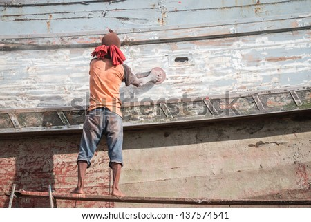 Boat Hull repairs/ A man using grinder in preparation for anti foul paint being applied - stock photo