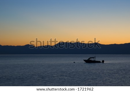 Boat in a lake during sunrise - stock photo