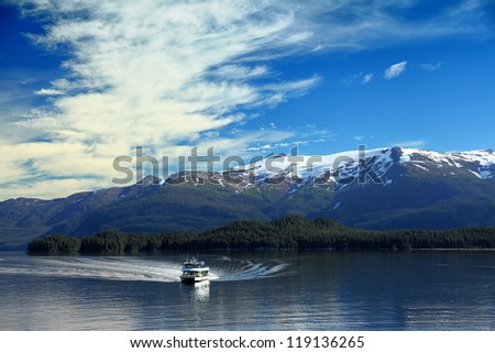 boat in alaska fjord with snow capped mountains - stock photo