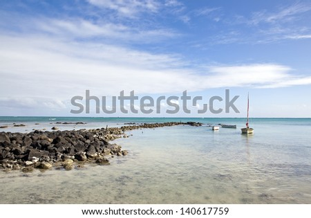 Boat in bay, rocky beach, Mont choisy beach, Mauritius island - stock photo