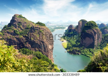 boat in calm waters amongst grotesque mountain - stock photo