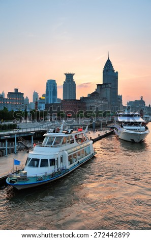 Boat in Huangpu River with Shanghai urban architecture at sunset - stock photo