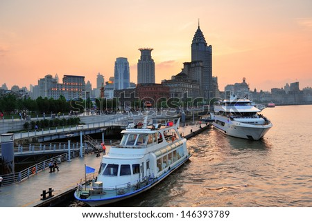 Boat in Huangpu River with Shanghai urban architecture at sunset in dock - stock photo