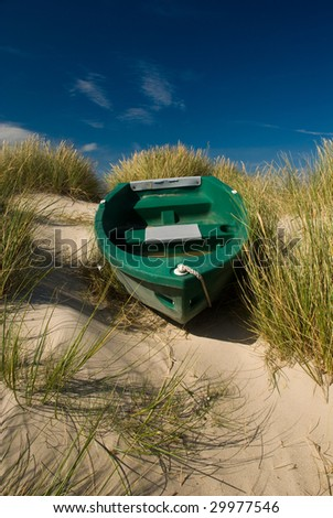 Boat in sand dunes. - stock photo