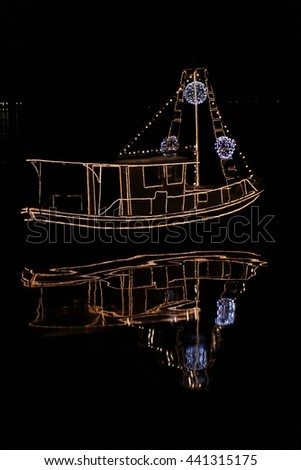 Boat in the dark illuminated with lighting hose and reflection in the water. - stock photo