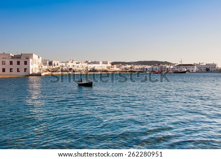 Boat in the sea bay near the town of Mykonos in Greece against the sky - stock photo