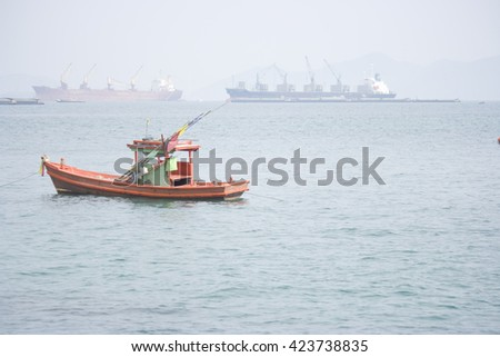 Boat in the sea. Cargo ships in the background.