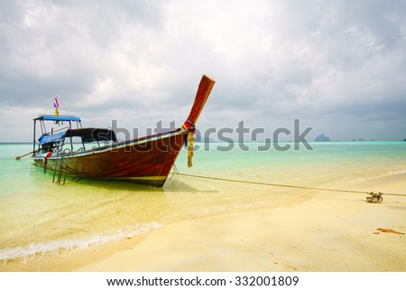Boat in turquoise sea and yellow sandy beach