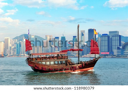 Boat in Victoria Harbor in Hong Kong with city skyline in the day - stock photo