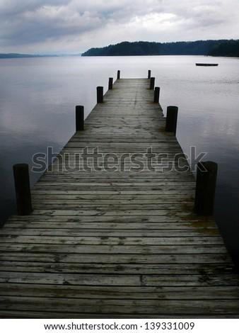 Boat jetty on silver lake and cloudy sky - stock photo