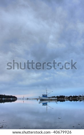 boat lying on the side at low tide - stock photo
