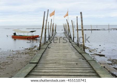 Boat moored at dock in tide low. - stock photo