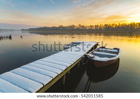 boat moored to the snow-covered bridge over the lake in winter morning
