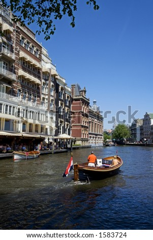 boat moving along a canal in Amsterdam - stock photo