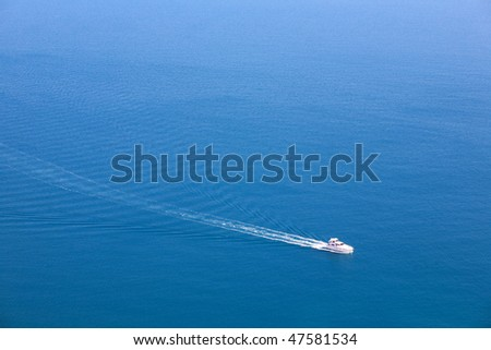 Boat moving on blue tranquil sea - stock photo