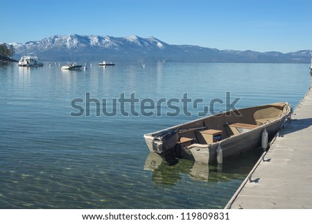 Boat near pier at the Lake Tahoe with snowy Mountain peaks in the background - stock photo