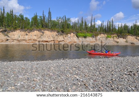 Boat off the coast of Northern rivers. Tourist catamaran on the pebbly Bank of the Ural river. - stock photo
