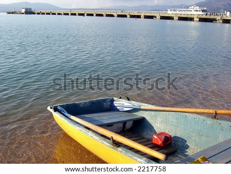 Boat on a sandy beach, the sea and a mooring. - stock photo