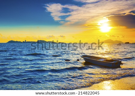 Boat on a sea coast at sunset - stock photo