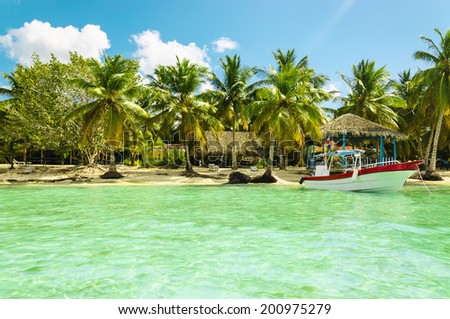 Boat on azure water on a background of exotic beach on one of the Caribbean Islands - stock photo