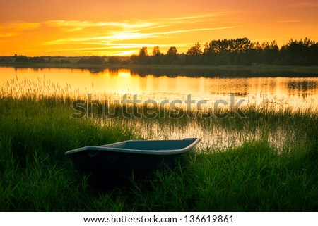 Boat on bank of river at sunset in grass - stock photo
