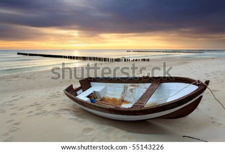 Boat on beautiful beach in sunrise - stock photo