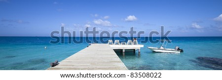 Boat on blue lagoon with a woman seat on chair of a pontoon in paradise island - stock photo