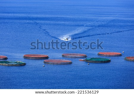 Boat on it's way to a fish farm in the Atlantic Ocean. - stock photo