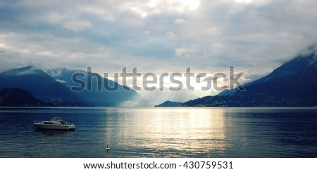 Boat on Lake Como at the sunset. Silver linings in Lake Como at the sunset. Retro style photo. Sunset view of the lake in Lombardy. Varenna, Lake Como, Italy. - stock photo